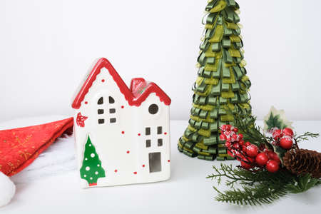 Christmas background with red ceramic decorative house, santa hat, pine fir tree and new year decorations against white.