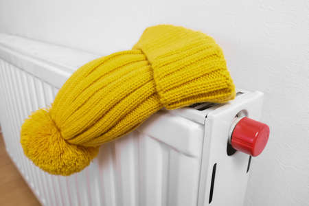 Colorful yellow winter knitted cap, hat hanging and drying on a hot central heating radiator, winter outdoor sport activities concept.