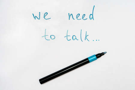 We need to talk message frase written on white piece of paper with a marker, communication problems in family or work office concept.