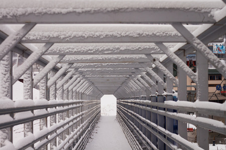 Wooden bridge, snow, transition resembles the tunnel.