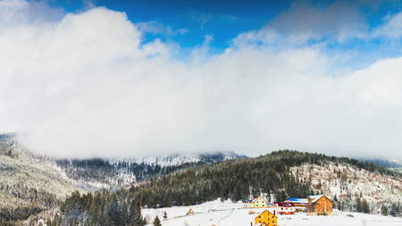 Clouds that are moving fast over the top of a snowy mountain in time laps.