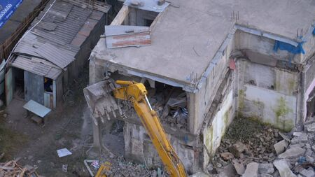 Destroying Old House Using Bucket Excavator on Construction Site. Banque d'images
