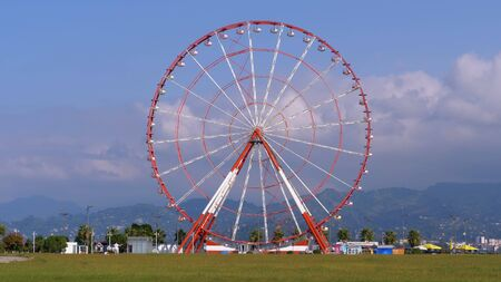 Ferris Wheel against the Blue Sky with Clouds near the Palm Trees in the Resort Town, Sunny Day Banque d'images