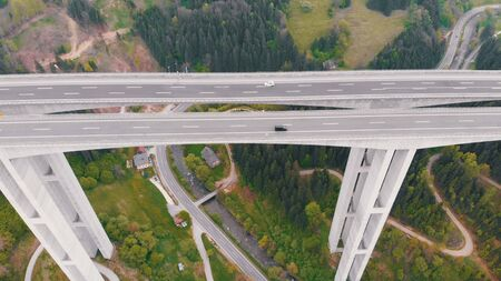 Aerial view of the Highway Viaduct on Concrete Pillars with Traffic in Mountains Banque d'images