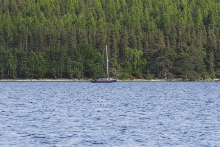 A lone boat cruising on Loch Ness Lake in Inverness, Scotland. Stock Photo