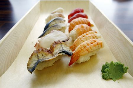 Japanese Food - a variety of traditional raw sushi and wasabi served on a wooden tray.