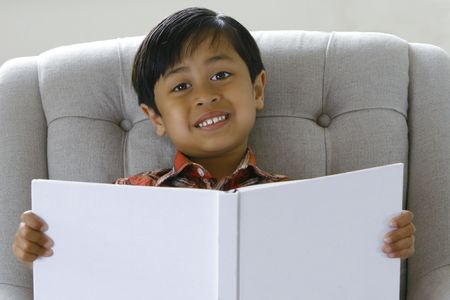 A 5 year old boy (asian origin) learning to read a book at home. Stock Photo