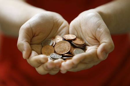 Two hands holding a handful of used coins (UK Pence) Stock Photo