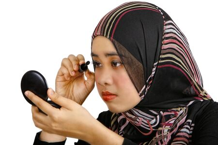 A young muslim women applying makeup