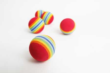5 colourful foam balls scattered on a white background. sharp focus on the front ball. Stock Photo