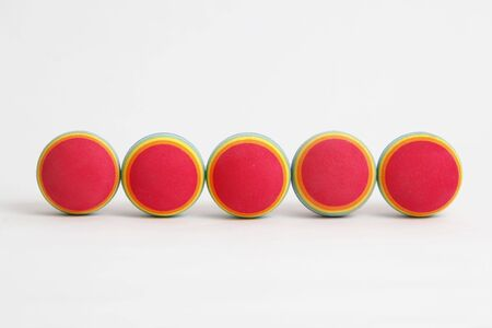 5 colourful foam balls in a line on a white background. Stock Photo