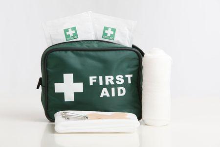 primeros auxilios: Kit de primeros auxilios con vendaje, yesos y toallitas aislados en un fondo blanco.