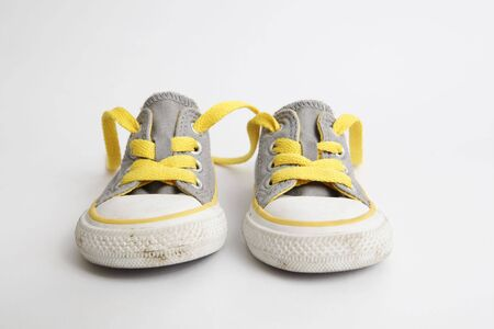 A fairly used childs shoesneaker on white background - front view
