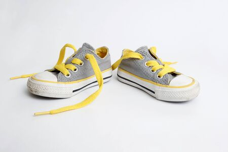 A fairly used childs shoesneaker on white background - side view