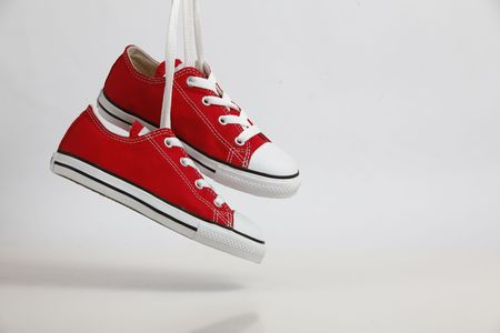 Red Shoe  Sneakers hanging with soft shadow - isolated on white. Plenty of copy space.  Stock Photo