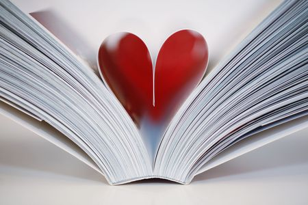 Open book with a heart symbol in the middle Stock Photo
