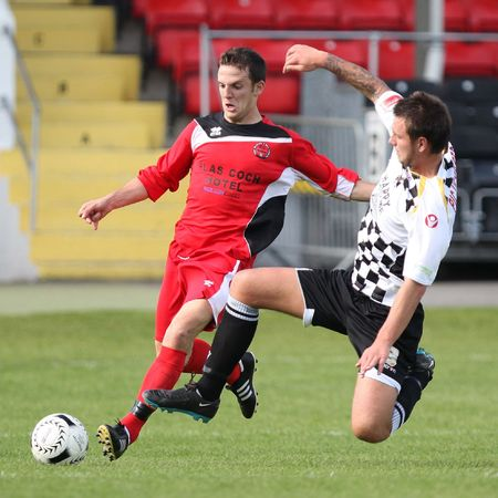 NEATH, WALES - SEPTEMBER 13: Marc Griffiths (left) of Bala Town is being challenged by Rory Smitham (right) of Neath Athletic during their Welsh Premier League match against Bala Town at The Gnoll Stadium, Neath. Neath won 2-1. Editorial