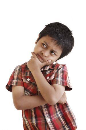 A young asian boy is thinking hard