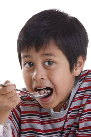 A young boy eating cereal for breakfast Stock Photo