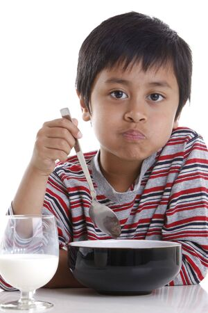 A young boy eating cereal and milk for breakfast