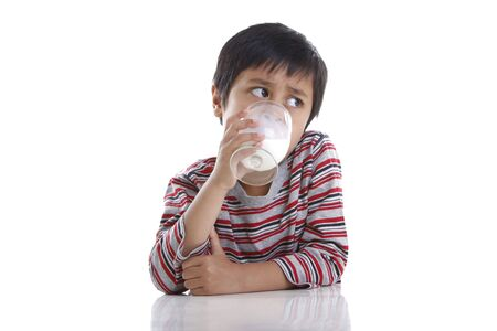 A young boy looks away while drinking a glass of milk Stock Photo