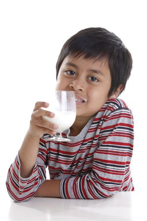 A young boy smile while drinking a glass of milk Stock Photo