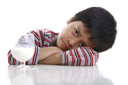 sullenly: A young boy refusing to drink his milk.