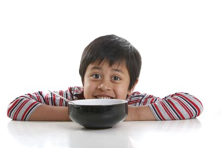A young boy is waiting for his bowl of cereal for breakfast