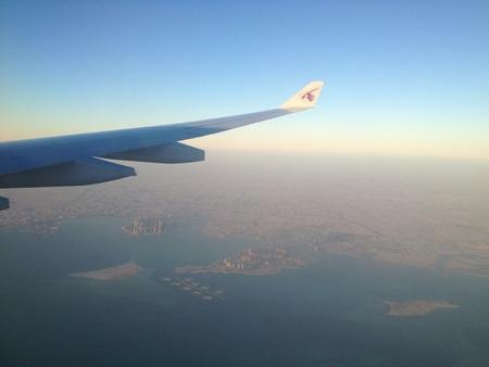 A Qatar Airways aircraft flying low over the city of Doha Qatar on approach to Qatar International Airport Standard-Bild
