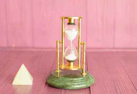 Sand glass beautiful clock with accessories on a pink background