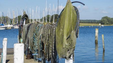 redes de pesca: Redes de pesca y trampas para peces por desecación en un estante de madera.