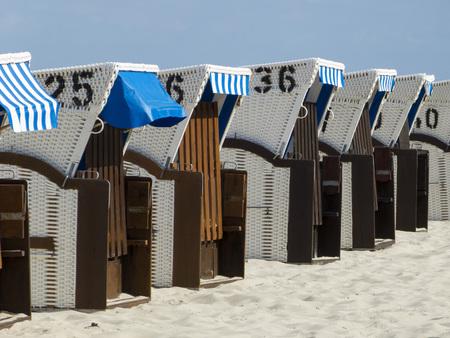 北海とバルト海の屋根付き籐ビーチチェア太陽から保護するため、木材やバスケットの仕事の雨、風、砂ビーチ椅子が作られました。 写真素材