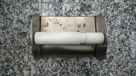 chrome: Empty toilet paper roll on marble wall Stock Photo