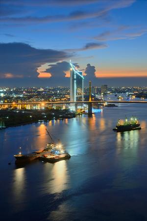 ix: Beautiful nightfall of Chao Phraya River, Many cargo ships docked in the middle river near the Rama 9 Bridge.