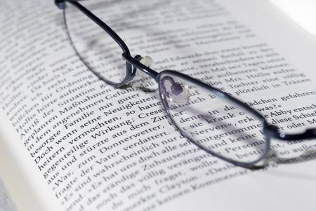 gafas de lectura: gafas para leer en el libro de Foto de archivo