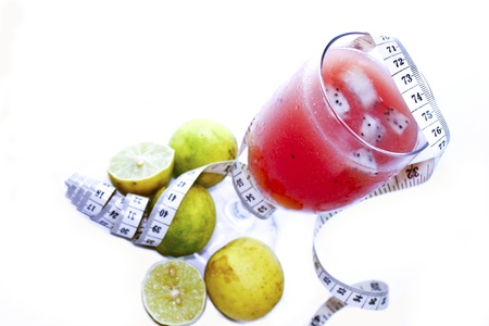 juice for diet on the white background with tape measure and lemons  photo