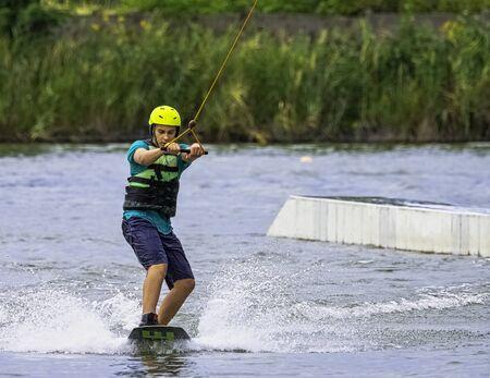 Teenager wakeboarding on a lake - Brwinow, Masovia, Poland Stock Photo