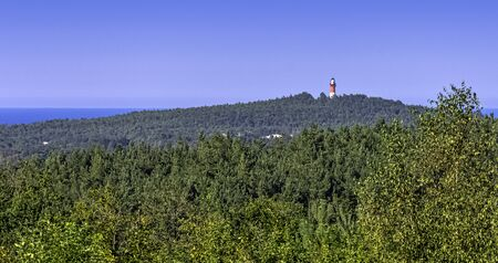 Panoramic view of lighthouse in Stilo with forest and Baltic Sea in background - Pomerania, Poland 免版税图像