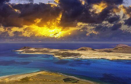 Amanecer sobre la isla volcánica de La Graciosa del Océano Atlántico - una vista desde Lanzarote, Islas Canarias, España