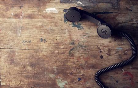 telefono antico: Retro ricevente di telefono sul vecchio tavolo in legno di sfondo