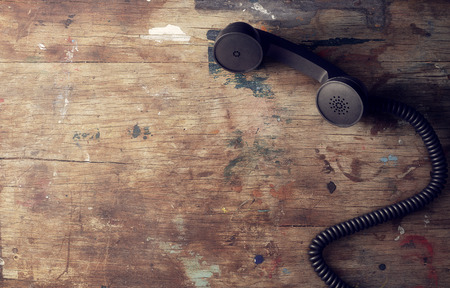 Retro telephone reciever on old wooden table background