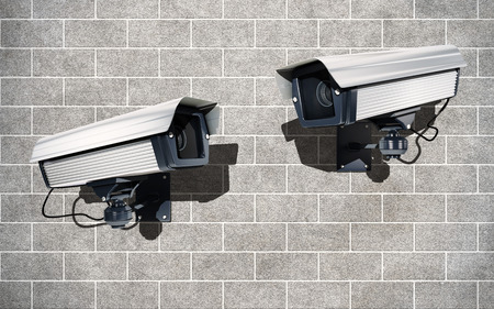 electrical materials: Surveillance Cameras watching each other onbrick wall