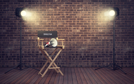 Film director's chair with megaphone and spotlights shining