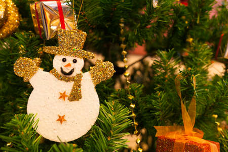 chirstmas: snowman decoration with blur chirstmas tree background Stock Photo