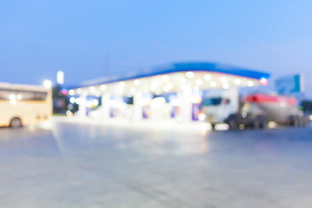 unleaded: out of focus twilight gas station with bus and concrete truck