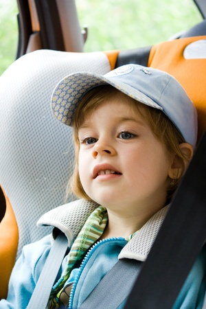 Happy smiling little girl seated in child seat in the car photo