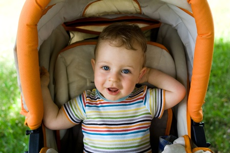 boy sitting: Happy young boy sitting in the baby carriage
