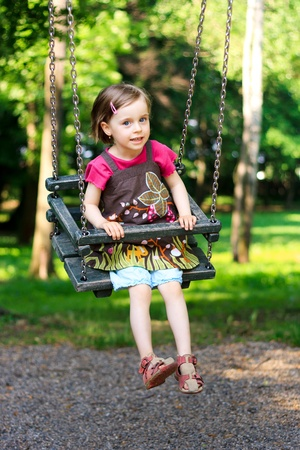 A beautiful little girl swinging at the playground in the park photo