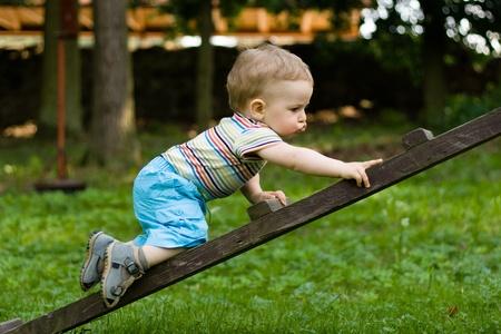 Happy jonge jongen kruipen op de ladder in het park