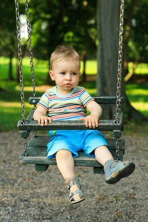 A handsome little boy swinging at the playground in the park photo